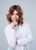 Femme d'affaires mignonne montrant le doigt au-dessus des lèvres Photographie stock