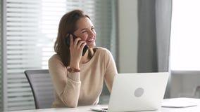 Femme d'affaires millénaire de sourire parlant au téléphone faisant l'appel d'affaires banque de vidéos