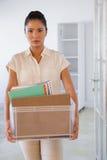 Femme d'affaires mise le feu tenant la boîte de ses choses photo stock