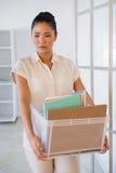 Femme d'affaires mise le feu tenant la boîte de ses choses photographie stock libre de droits
