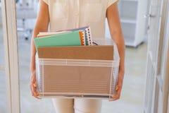 Femme d'affaires mise le feu tenant la boîte de ses choses images stock