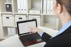Femme d'affaires montrant à l'ordinateur portable Images stock