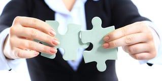 Femme d'affaires montrant deux morceaux de puzzle denteux Photographie stock libre de droits