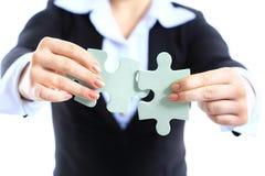 Femme d'affaires montrant deux morceaux de puzzle denteux Images stock