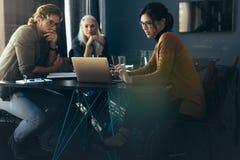 Femme d'affaires montrant l'analyse de projet aux collègues photos libres de droits