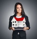 Femme d'affaires montrant la maison symbolisant la vente de Photo stock
