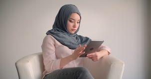 Femme d'affaires musulmane dans le hijab observant dans le comprim? attentivement ?tant immerg? dans le travail dans le fauteuil banque de vidéos