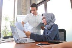 Femme d'affaires musulmane et homme bel collaborant avec le comprimé et le papier d'ordinateur portable près des fenêtres avec le photo stock