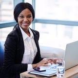 Femme d'affaires noire souriant à l'appareil-photo devant l'ordinateur Image stock