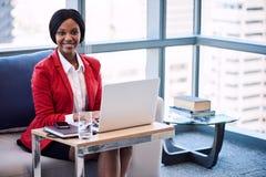 Femme d'affaires noire souriant à l'appareil-photo tandis qu'assis sur le sofa Photos stock
