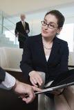 Femme d'affaires observant des contrats dans l'entrée moderne. Images libres de droits