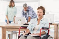 Femme d'affaires occasionnelle dans le fauteuil roulant prenant des notes Photographie stock