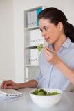 Femme d'affaires occasionnelle de brune mangeant d'une salade à son bureau images stock