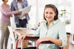 Femme d'affaires occasionnelle de sourire dans le fauteuil roulant Images stock