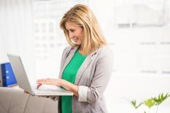 Femme d'affaires occasionnelle de sourire travaillant avec l'ordinateur portable Photo libre de droits