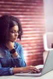 Femme d'affaires occasionnelle employant l'ordinateur portable et le smartwatch Images stock