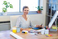 Femme d'affaires occasionnelle regardant l'échantillon de couleur et dessinant avec le convertisseur analogique-numérique photographie stock