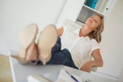 Femme d'affaires occasionnelle s'asseyant à son bureau avec des pieds  Images libres de droits