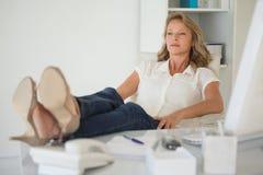 Femme d'affaires occasionnelle s'asseyant à son bureau avec des pieds  Image stock