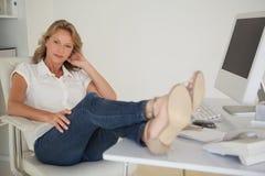 Femme d'affaires occasionnelle s'asseyant à son bureau avec des pieds  Photos stock