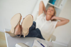 Femme d'affaires occasionnelle s'asseyant à son bureau avec des pieds  Photo libre de droits