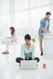 Femme d'affaires occasionnelle s'asseyant sur le plancher utilisant l'ordinateur portable Images stock