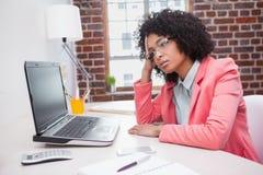 Femme d'affaires occasionnelle soumise à une contrainte s'asseyant au bureau Photos libres de droits