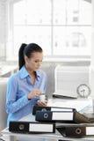 Femme d'affaires occupée ayant le café au bureau Images libres de droits