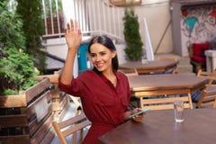 Femme d'affaires occupée soulevant sa main appelle le serveur Image stock