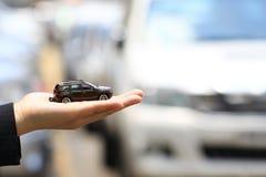 Femme d'affaires ou vendeuse tenant le modèle miniature de voiture, commerce de l'automobile, commerce de voiture, prêts pour le  image stock
