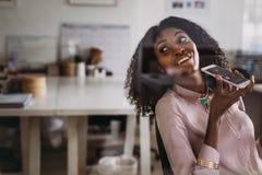Femme d'affaires parlant au-dessus du téléphone portable sur le haut-parleur tandis que wor photo stock
