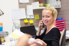 Femme d'affaires parlant au téléphone portable acceptant des papiers photos libres de droits