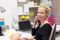 Femme d'affaires parlant au téléphone portable acceptant des papiers Photographie stock