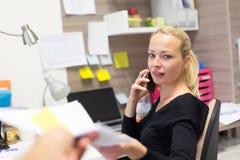 Femme d'affaires parlant au téléphone portable acceptant des papiers Images libres de droits
