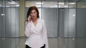 Femme d'affaires parlant au téléphone portable dans le couloir du bureau banque de vidéos