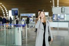 Femme d'affaires parlant par le smartphone au hall d'aéroport, au manteau gris de port et au sac Image stock