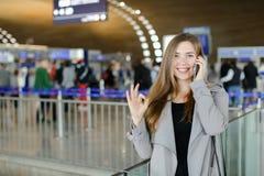 Femme d'affaires parlant par le smartphone au hall d'aéroport, au manteau gris de port et au sac noir, montrant correct Image libre de droits