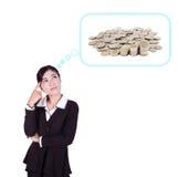 Femme d'affaires pensant aux piles des pièces de monnaie Images stock