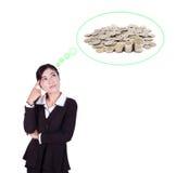 Femme d'affaires pensant aux piles des pièces de monnaie Photographie stock