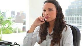 Femme d'affaires pensant tout en tenant un stylo Photographie stock libre de droits