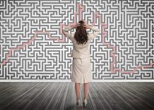 Femme d'affaires perplexe regardant un labyrinthe Images libres de droits