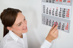 Femme d'affaires Placing Red Mark On Calendar Date Photo stock