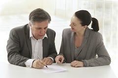 Femme d'affaires poiting un document à l'homme d'affaires Photographie stock libre de droits