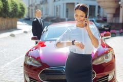 Femme d'affaires positive gaie vérifiant le temps Image stock