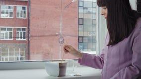 Femme d'affaires préparant les nouilles instantanées à la fenêtre contre un immeuble de brique banque de vidéos