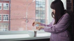 Femme d'affaires préparant les nouilles instantanées à la fenêtre contre un immeuble de brique clips vidéos