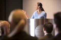 Femme d'affaires présentant l'exposé au podiume