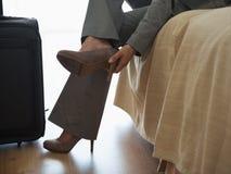 Femme d'affaires prenant des chaussures hors fonction dans la chambre d'hôtel photo stock