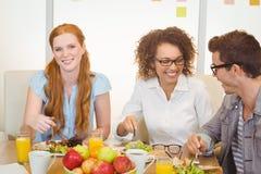 Femme d'affaires prenant le déjeuner avec des collègues Images stock