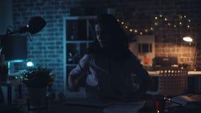 Femme d'affaires quittant le lieu de travail tard la nuit arrêtant la lumière et l'ordinateur portable banque de vidéos